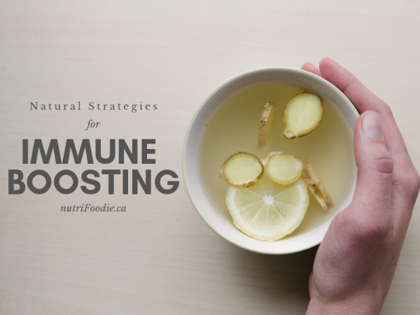 Natural Immune-boosting Strategies - hand holding cup of tea with ginger and lemon